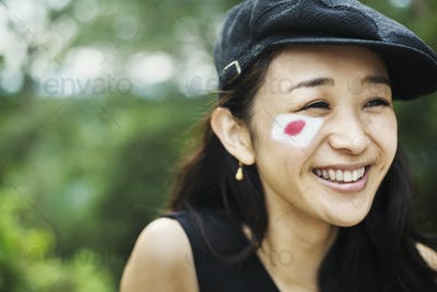 Young woman with black hair wearing flat cap, Japanese flag painted on her cheek.