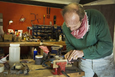 A knife maker in a workshop carefully putting the blade of a kitchen knife into a clamp