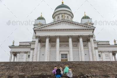 Women walking up the steps of the Lutheran Cathedral in Helsinki, Finland.
