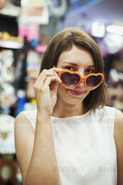 Young woman wearing orange heart shaped sunglasses, looking at camera.