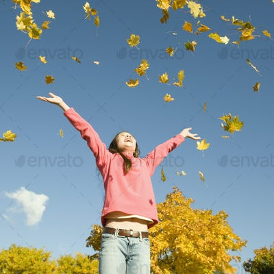 A girl throwing dried fallen autumn leaves high into the air.