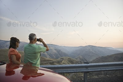 An Hispanic senior couple enjoying the scenery from a rest stop on a highway