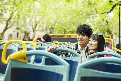 Smiling man and woman on the top of an open Double-Decker bus on a tour