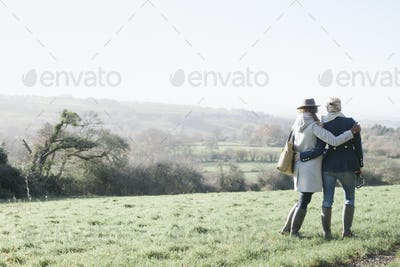 Two women side by side on a grass slope overlooking the landscape of Dorset.