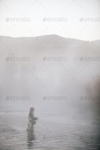 A woman fisherman flyfishing, standing in waders in thigh deep water.