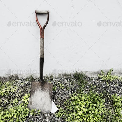 An old shovel propped against a wall.