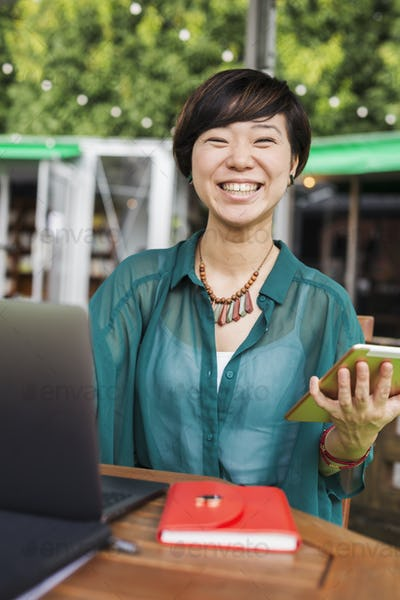 Woman using a laptop at table in a street cafe, holding digital tablet