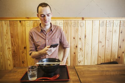 A western man in a noodle restaurant, using his smart phone.