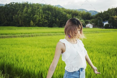 A young woman with hands outstretched, standing in rice paddy fields.