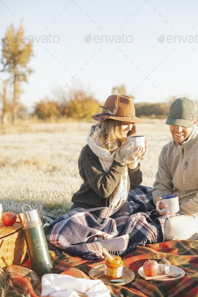 Two people, a couple on a winter picnic, seated on a tartan rug, holding hot drinks.