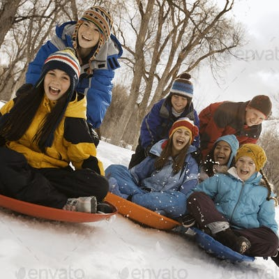A group of children, boys and girls, riding on sledges on the snow.