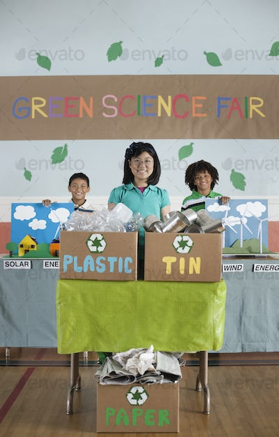Three children standing behind presentations at the Green Science Fair.
