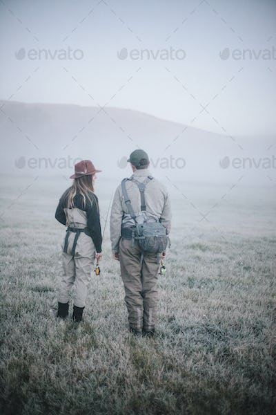 Two people walking across a meadow in early morning mist carrying fishing rods.