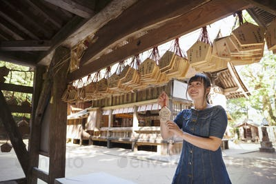 Young woman looking at wooden fortune telling plaques at shrine