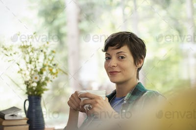 A woman holding a china cup in her hands.