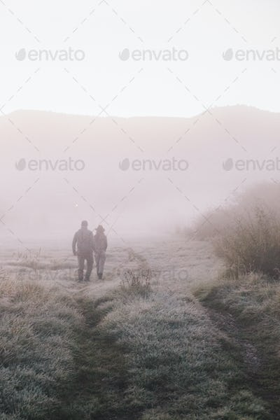 Two people, a man and woman walking along a path on a frosty morning.