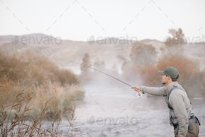 A man standing casting his fishing rod, flyfishing from a riverbank.