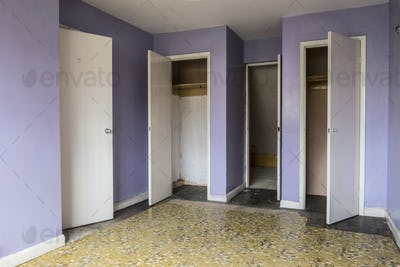 Empty bedroom with yellow floor and lilac walls in abandoned house, white wardrobe doors.