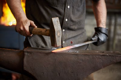 An artisan metal worker shaping a red hot piece of metal on an anvil.