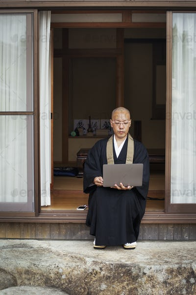 Buddhist monk sitting outside temple looking at laptop computer.