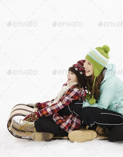Two children sitting on a sledge on the snow.