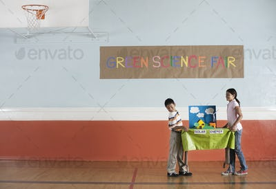 A boy and girl carrying a table with a presentation on solar power, at a Green Science Fair event.