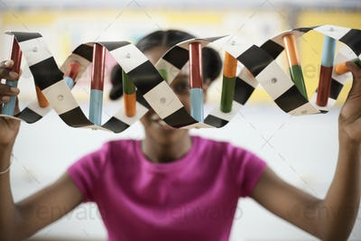 A girl in a science class holding a model of a helix structure in front of her face.