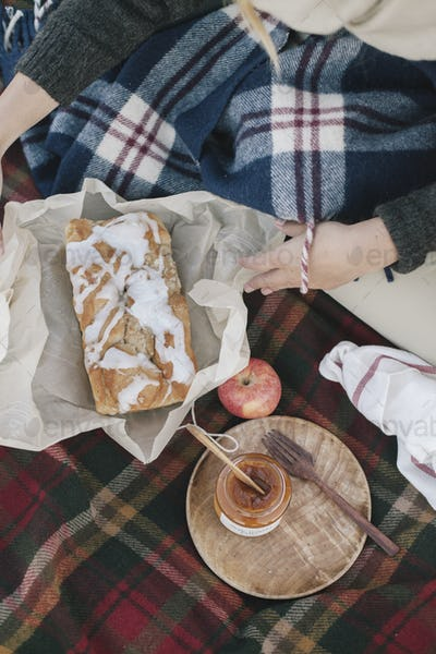 View from overhead of two people at a picnic, one unwrapping a loaf cake.