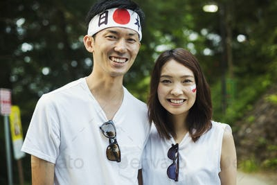 Man wearing headband and young woman with Japanese flag painted on her cheek,
