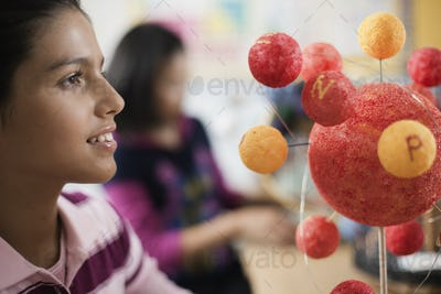 A group of students around a desk in a science lesson, creating molecular models.