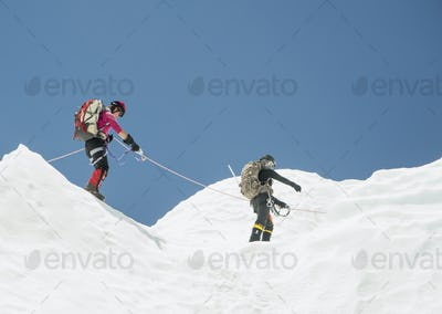 Two climbers in snow on a mountain, roped together.
