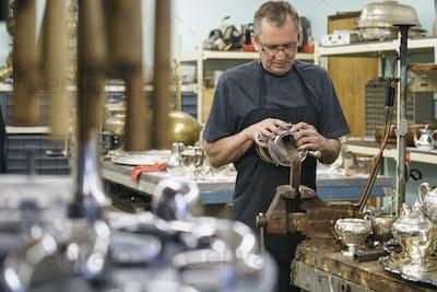 Silversmith restoring silver cup in workshop.