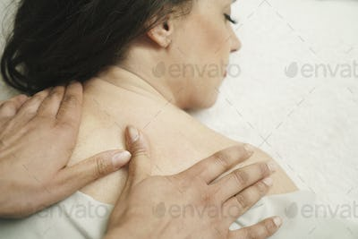 Masseuse giving woman neck massage at health and beauty clinic, elevated view.
