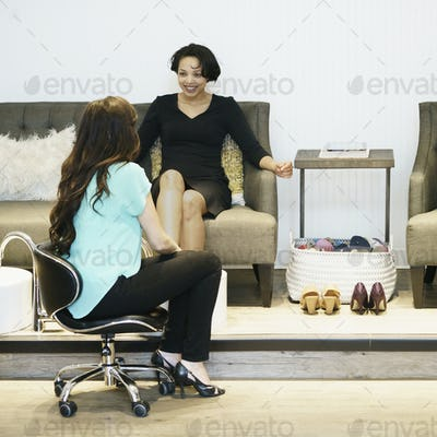Two women sitting chatting at health and beauty clinic, smiling.