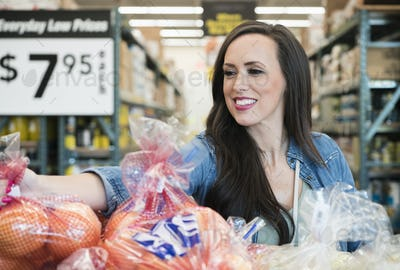 Mid adult woman smiling in grocery store, reaching for vegetables.