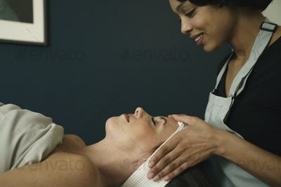 Therapist giving woman head massage at health and beauty clinic.
