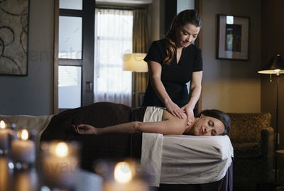 Masseuse giving woman neck massage at health and beauty clinic.