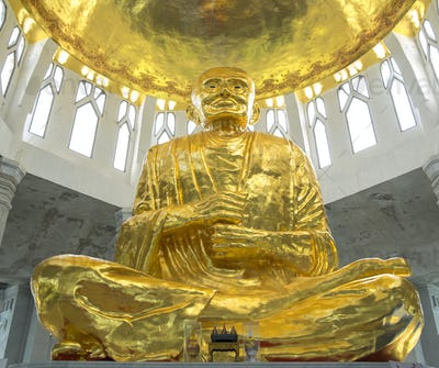 Low angle view of golden Buddha statue in temple, Sikhiu, Nakhon Ratchasima, Thailand
