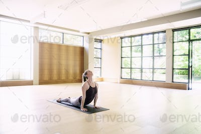 Woman stretching in yoga position at gym.