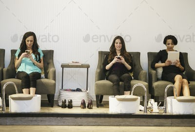 Three women using mobile devices while having foot spa treatment at health and beauty clinic.