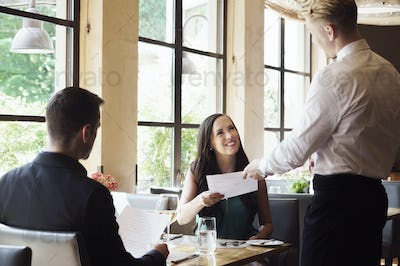 Couple being served by waiter at restaurant table.