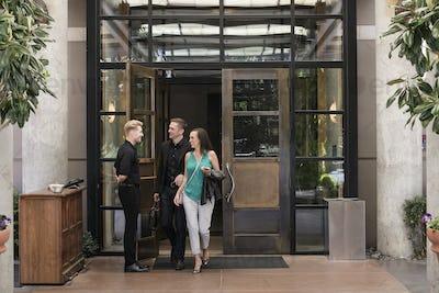 Bellhop opening door for hotel guests.