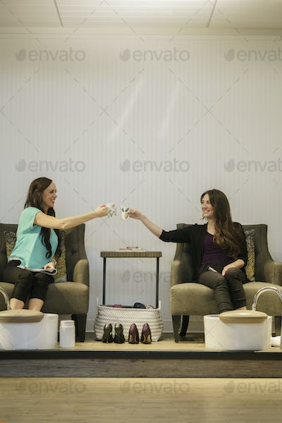 Two women clinking cups while having foot spa treatment at health and beauty clinic.