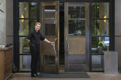 Bellhop standing at wooden reception desk of a downtown hotel.