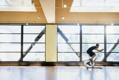 Man on exercise bike in gym, side view.