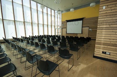 Chairs and projection screen in empty room