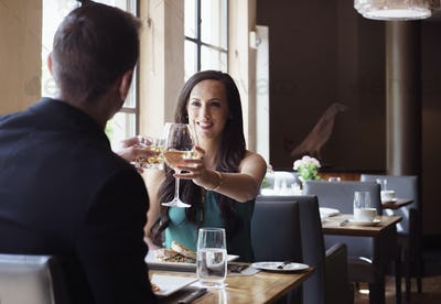 Couple celebrating in a restaurant raising their glasses in a toast.