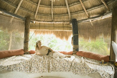 Young woman laying on bed in hut