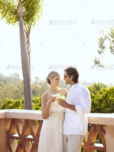 Glamorous Caucasian couple drinking cocktails outdoors