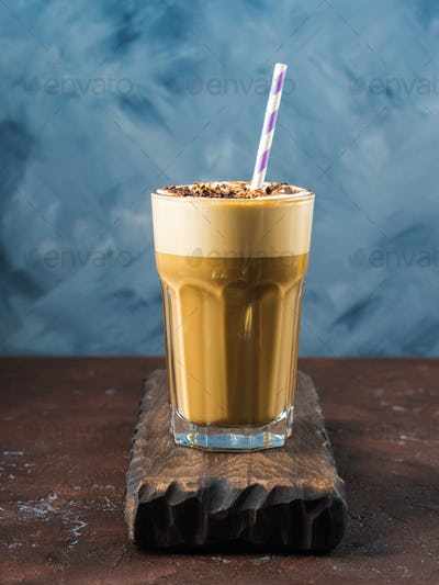 Frappe coffee in tall glass on blue and brown